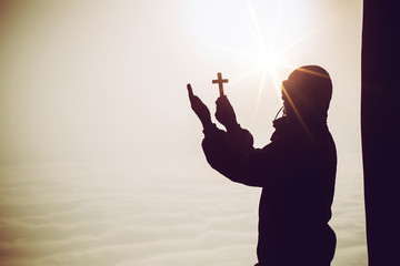 Christian people praying to Jesus christ with dramatic sky background