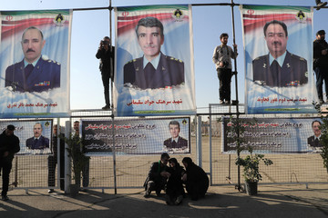 Pictures of the victims of Boeing 707 military cargo plane crash are seen during a funeral at Mehrabad Airport in Tehran