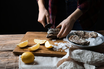Woman opening raw oyster with knife at table