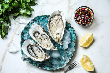 Plate with tasty cold oysters on light table