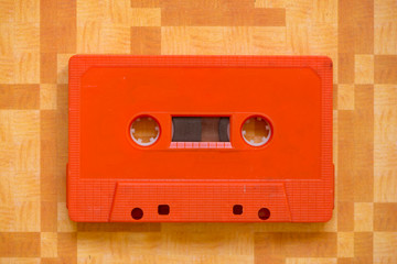 An orange cassette tape on an original background