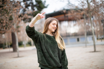 Happy young woman jumping and enjoying with injured arm in the park