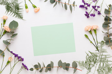 Flowers composition. Paper blank, carnation flowers, eucalyptus branches on pastel  background. Flat lay, top view, copy spaceFlat lay stiil life.