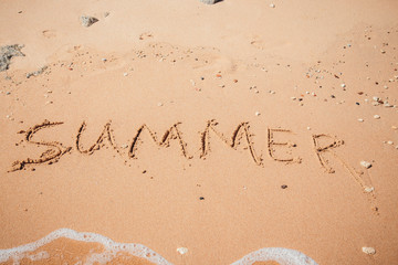 Inscription on wet sand Summer. Concept photo of summer vacation.