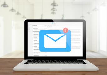 laptop mail on wooden desktop