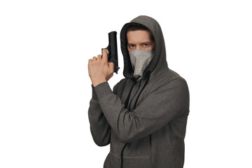 The man in a sports jacket and in a mask on a face shoots with the gun. White background