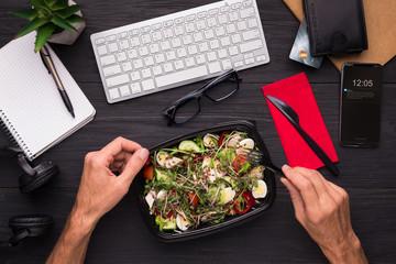 Businessman enjoying healthy salad at work desk
