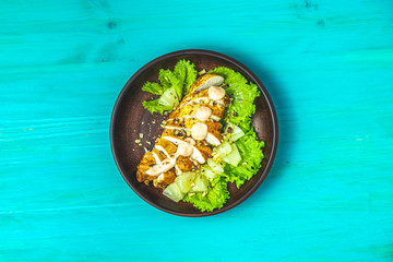 Chicken with pineapple, lettuce, cream sauce and walnut in ceramic plate