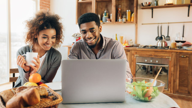 African-american man working on laptop in kitchen
