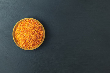 Red lentils in wooden plate on black stone table background