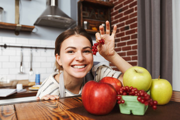 Happy young woman standing at the kitchen at home