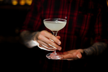 Bartender serving a glass of a Courpse Reviver cocktail on the bar counter
