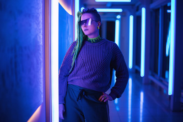 Neon girl with with green and purple dreadlocks in sunglasses