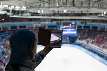 Girl writes video or takes pictures of figure skating competitions on the tablet