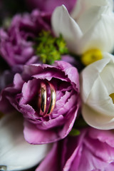 Gold wedding rings on the bride's bouquet, close-up