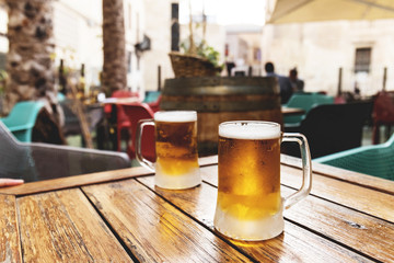 Ice cold inviting beer for two for refreshing the summer heat at the bar table