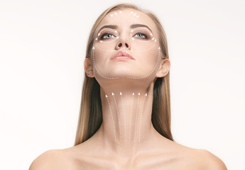 Close-up portrait of young, beautiful and healthy woman with arrows on her face. The spa, surgery, face lifting and skin care concept Fototapete