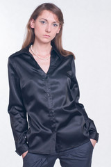 Beautiful young woman in black shirt and trousers on bright background. Fashion studio shoot