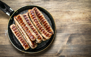 Fried sausages in a frying pan.