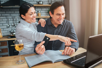 Happy woman sit with man at table in kitchen. She point on laptop. Guy look at it. They smile. He hold handson journal. Glass of wine stand on table.