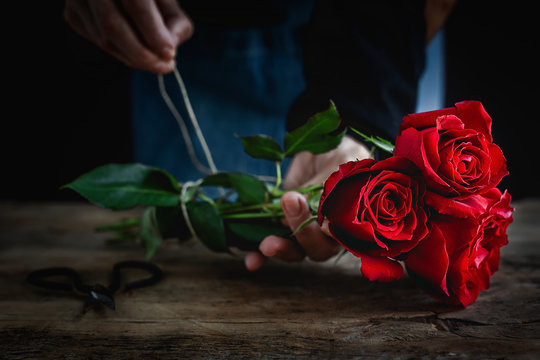 Unrecognizable woman making a bouquet of red roses