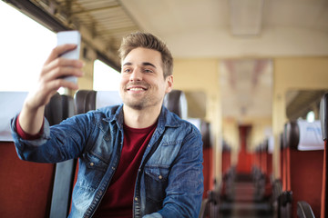 Handsome guy traveling on a train, taking a selfie