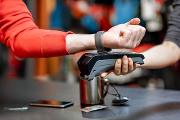 Man using handwatch on the cash register for buying goods at the sports shop, close-up view with no face