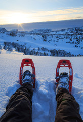 Hiker looking over his snowshoes at the snowcovered hills during a winter sunset.