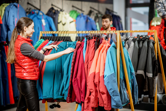 Young woman choosing winter clothes picking up down jackets on the hanger in the sports shop