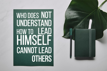 """Green stationery set and monstera leaf on white marble background with """"who does not understand how to lead himself cannot lead others"""" lettering"""