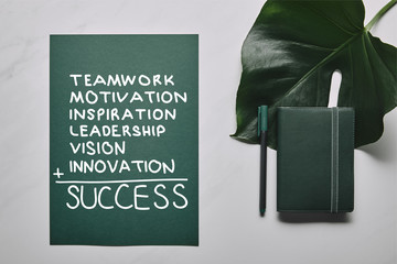 """Green stationery set and monstera leaf on white marble background with """"success"""" inspiration"""