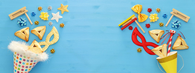 Purim celebration concept (jewish carnival holiday) over wooden blue background. Banner.