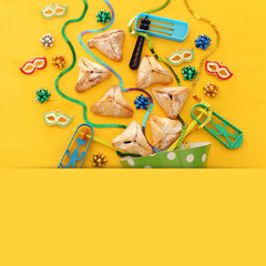 Purim celebration concept (jewish carnival holiday) over wooden yellow background.