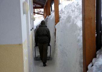 An Austrian army member shovels snow after heavy snowfall in Werfenweng