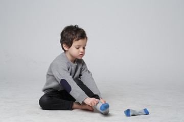 Portrait of Cute little kid sitting  learning how to put the socks on by him self, Happy Toddler boy pulling his socks to his foot, Child development concept