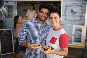 Smiling couple standing with snacks