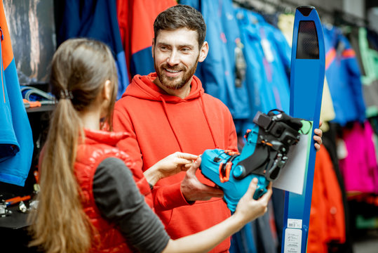 Man and woman choosing sports equipment looking on the ski and boots for skiing in the shop