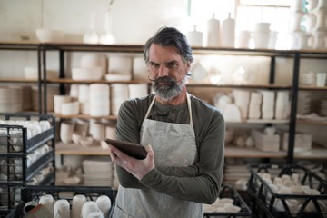 Serious potter using tablet surrounded by work