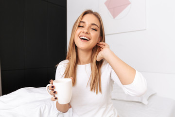 Happy young girl sitting on bed in the morning