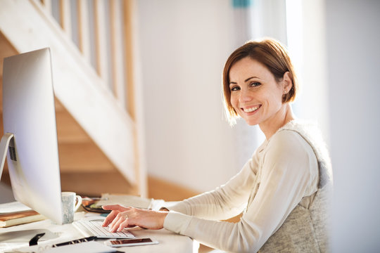 A happy young woman indoors, working in a home office.