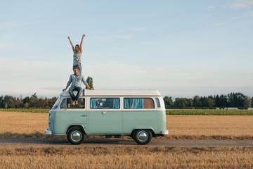Happy couple on roof of a camper van in rural landscape