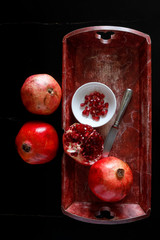 Whole pomegranate and pomegranate seed with bowl and knife on wooden tray