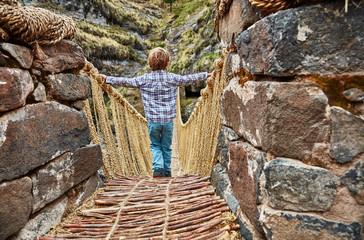Peru, Quehue, boy crossing rope bridge