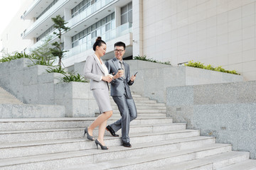 Young Asian couple drinking coffee when walking down the stairs