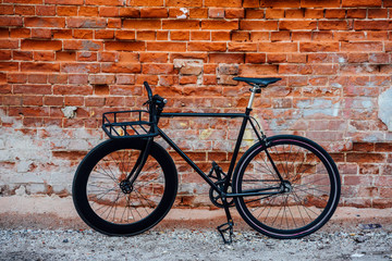 Customised commuter fixie bike at brick wall