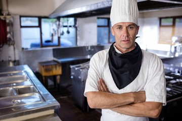 Male chef standing with arms crossed in kitchen