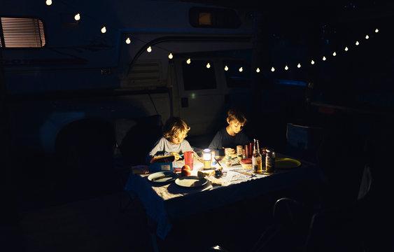 Brazil, Bonito, two boys drawing at camper in the dark
