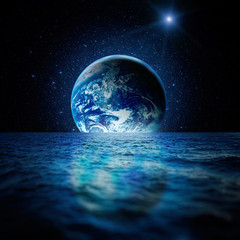 Fantastic space landscape. Planet Earth is reflected in the waters of the ocean with a myriad of stars. Elements of this image furnished by NASA.
