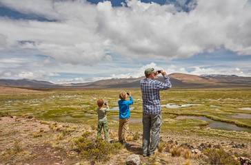 Peru, Chivay, Colca Canyon, father and sons taking pictures of swamp landscape in the Andes