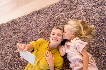 Smiling mother and daughter lying on carpet taking a selfie